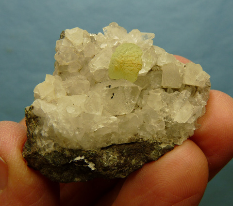 A small, well-formed prehnite crystal with other crystals on matrix