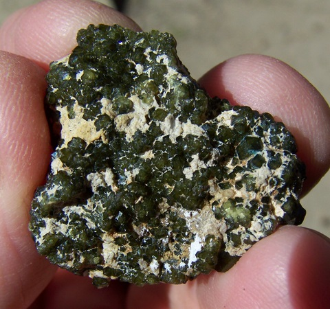 Druse of gemmy demantoid garnets on matrix