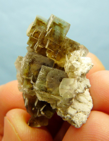 A cluster of greyish-brown fluorite crystals, some with darker centres and patterns inside