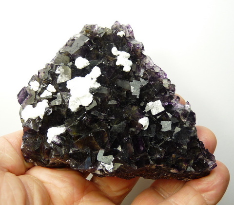 Dark (mostly purple) fluorite crystals with feldspar, on matrix