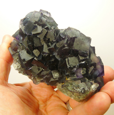 Lovely cluster o fdark green fluorite crystals with bits op purple colouring